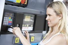 Woman Using Her Debit Card To Pay For Gasoline Stock Photos