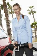 Mid Adult Woman Refueling Her Car - stock photo