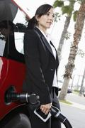 Business Woman Refueling Her Car - stock photo