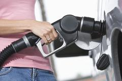 Woman Refueling Her Car At A Fuel Station - stock photo