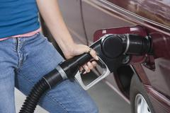 Mid Section Ff A Woman Refueling Her Car - stock photo