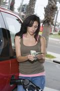 Woman Counting Money While Refueling Car - stock photo