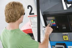 Man Using His Debit Card To Pay For Gasoline At Pump - stock photo