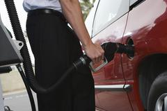 Mid Section Of A Businessman Refueling His Car - stock photo