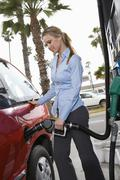 Woman In Formal Wear Refueling Her Car - stock photo
