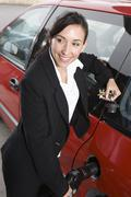 Business Woman In Suit Refueling Her Red Car - stock photo
