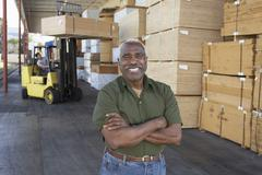 Portrait Of A Senior Man With Man Driving Forktruck In The Background - stock photo