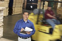 Man With Clipboard In Front Of Forklift In Warehouse Stock Photos