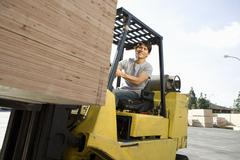 Happy Man Driving Forklift Loader - stock photo