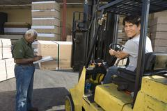 Worker Driving Forktruck And Senior Man Writing On The Clipboard - stock photo