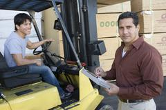 Man Writing On A Clipboard With Worker Driving Forktruck At Warehouse Stock Photos