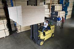 Worker Operating A Forklift Truck In Lumber Industry Stock Photos