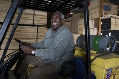 Warehouse Worker Sitting In Forklift Stock Photos