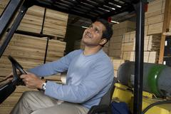 Warehouse Worker Sitting In Forklift And Looking Up Stock Photos