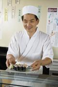 Chef Holding Plate Of Sushi In Restaurant - stock photo