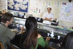 People Having Sushi In Japanese Restaurant Stock Photos
