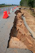 Cutting surface of asphalt road inner structure scouring by water flood attac Stock Photos