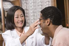 Optician Assisting Male Patient - stock photo