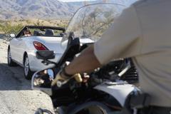 Police Officer On Motorbike Stopping Car On Desert Road Stock Photos