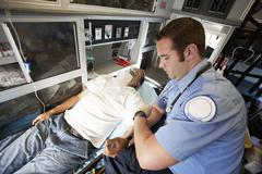 EMT Professional Taking Pulse Of A Man Stock Photos
