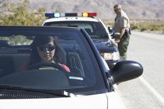 Woman In Car Being Pulled Over By Police Officer - stock photo