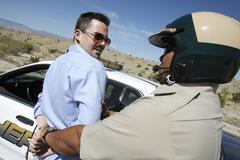Cop Arresting Middle Aged Man - stock photo