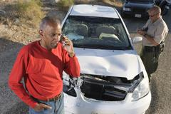 Senior Man On Call With Traffic Cop Writing Ticket - stock photo