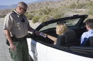 Cop Checking Woman's License Stock Photos