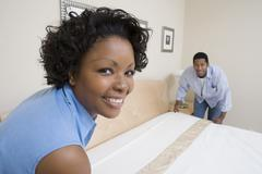 Couple Arranging Bed At Home Stock Photos