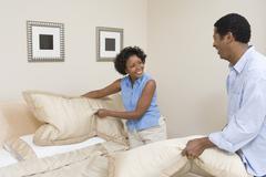 Couple Arranging Pillows On Bed Stock Photos