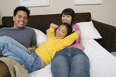 Happy Family Relaxing In Bedroom Stock Photos