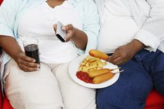 Midsection Of Overweight Couple With Junk Food Holding Remote Control Stock Photos