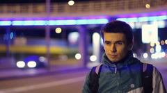 Young adult male tourist catches cars, night hitch-hiking, bag Stock Footage