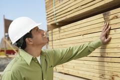 Construction Worker In Hardhat Inspecting Lumber - stock photo