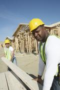 Stock Photo of Workers Stacking Boards At Construction Site