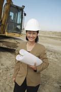Female Architect In Hardhat With Blueprints At Construction Site - stock photo