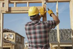 Construction Worker Working On Timber Frame - stock photo