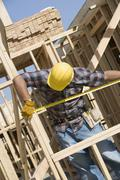 Foreman Measuring Framework At Construction Site - stock photo
