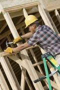 Man Hammering Nail On Wooden Formwork - stock photo
