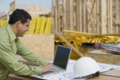 Engineer Working On Laptop At Site - stock photo