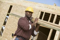 Stock Photo of Worker Carrying Wooden Beam On Shoulder