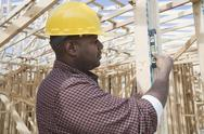 Stock Photo of Worker Using Spirit Level At Site