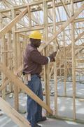 Worker Hammering On House Frame - stock photo
