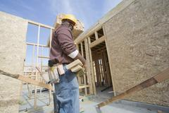 Stock Photo of Worker Carrying Wooden Beam At Site