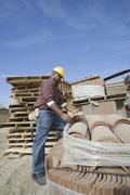 Worker Picking A Tile At Site - stock photo