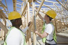 Workers Measuring Level Of Wooden Beam Stock Photos