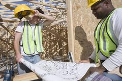 Stock Photo of Workers Examining Plan At Site