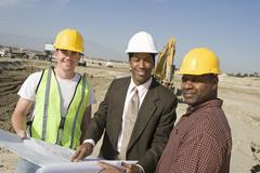 Foreman And Workers With Blueprint At Site - stock photo