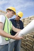 Supervisor And Co-Worker With Blueprint Stock Photos