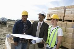 Architect And Workers At Construction Site - stock photo